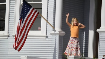 Margaret White, 5, waves from her porch as floats and marchers assemble for the start of the annual Fourth of July parade Wednesday, July 4, 2012 in Sausalito, Calif. (AP Photo/Eric Risberg)