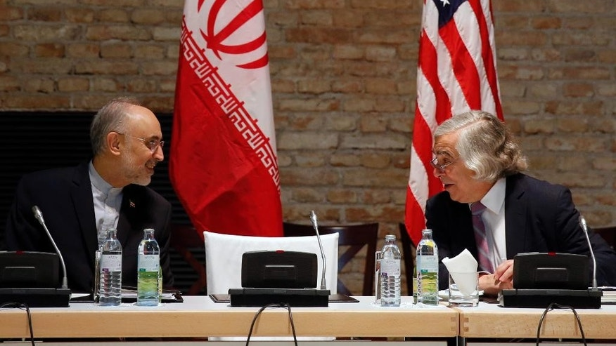 U.S. Secretary of Energy Ernest Moniz and Head of the Iranian Atomic Energy Organization Ali Akbar Salehi, left, meet at an hotel in Vienna, Thursday, July 9, 2015. Negotiations over Iran's nuclear program lurched toward another deadline on Thursday with diplomats reconvening amid persistent uncertainty and vague but seemingly hopeful pronouncements from participants. (Carlos Barria/Pool Photo via AP)