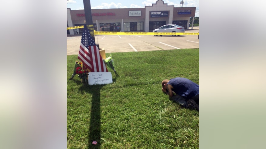 July 16, 2015: In this image made from video and released by WRCB-TV, a person lies on the grass near a makeshift memorial at the scene of a shooting in Chattanooga, Tenn. (Josh Rhoden/WRCB-TV via AP)