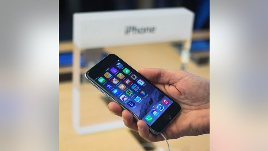 FILE -- September 19, 2014: A customer holds an iPhone 6 on display at the Fifth Avenue Apple store on the first day of sales in Manhattan, New York.