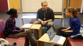 FILE -- English teacher Tom Rademacher talks with his high school juniors Kierra Murray, left, and Ana Silverman, right, at Fair School in Minneapolis.