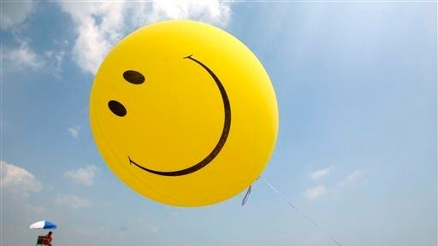 FILE - July 16, 2006: A smiley face balloon floats over Revere Beach in Revere, Mass. as beachgoers head for the water.