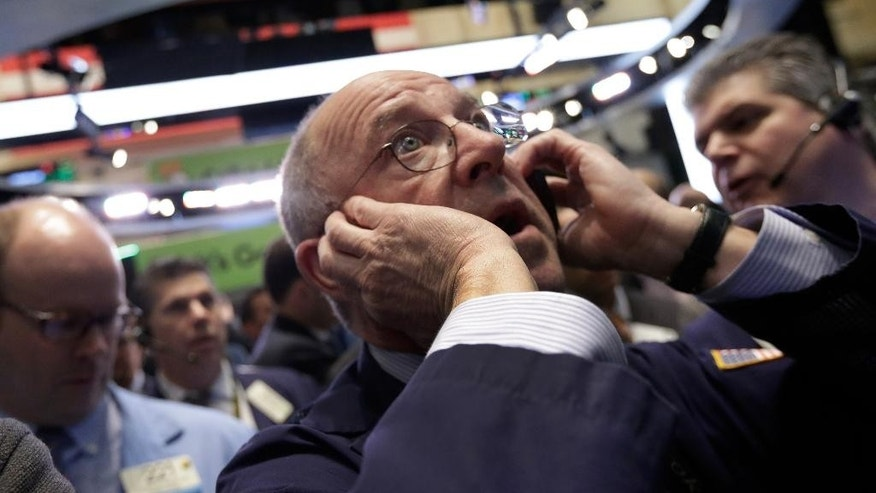Trader Frederick Reimer works on the floor of the New York Stock Exchange, Wednesday, April 1, 2015. U.S. stocks moved lower in early trading Wednesday, extending losses from the day before. A report indicating that U.S. businesses slowed their pace of hiring last month weighed on the market. (AP Photo/Richard Drew)