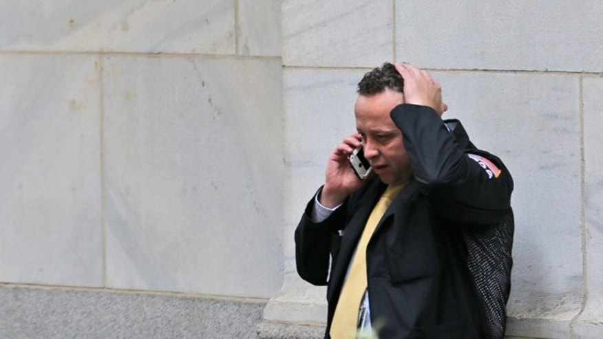 August 24, 2015: A trader talks on his phone in front of the New York Stock Exchange. U.S. stock markets plunged in early trading Monday following a big drop in Chinese stocks. (AP Photo/Seth Wenig)