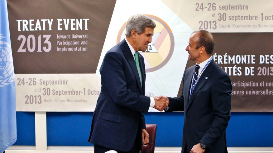 FILE -- Sept. 25, 2013: Secretary of State John Kerry, left, shakes hands with Under Secretary-General for Legal Affairs Miguel Serpa Soares after signing the Arms Trade Treaty during the 68th session of the United Nations General Assembly at U.N. headquarters.