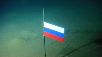 FILE - In this Thursday, Aug. 2, 2007 file made available by the Association of Russian Polar Explorers on Wednesday, Aug. 8, 2007, photo a titanium capsule with the Russian flag is seen seconds after it was planted by the Mir-1 mini submarine on the Arctic Ocean seabed under the North Pole during a record dive. Russia says it has submitted its bid for vast territories in the Arctic to the United Nations. The Foreign Ministry said Tuesday, Aug. 4, 2015, that Russia is claiming 1.2 million square kilometers (over 463,000 square miles) of Artic sea shelf.  (AP Photo/Association of Russian Polar Explorers, file)