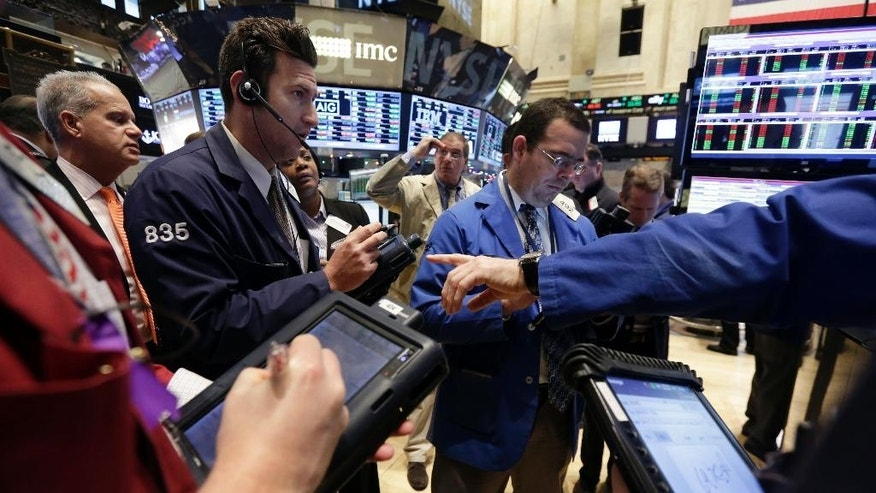 FILE -- Jan. 6, 2015: Traders gather at a post on the floor of the New York Stock Exchange. The U.S. stock market is edging higher in early trading as the price of oil extends its slump.