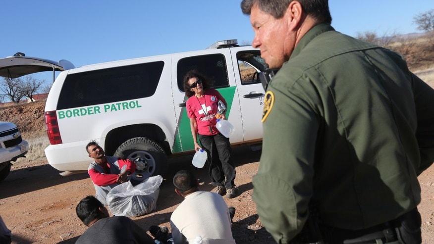 WALKER CANYON, AZ - MARCH 06:  U.S. Border Patrol agents guard a group of Mexican immigrants caught after they crossed illegally into the United States on March 6, 2013 near Walker Canyon, Arizona. Elisa Hauptman, a volunteer for the non-profit Samaritans group, arrived to offer water to the detained immigrants. Due to broad federal sequestration budget cuts, Border Patrol agents are expected to begin taking unpaid furlough days in April, as Customs and Border Protection funding is expected to be reduced by more than $500 million.  (Photo by John Moore/Getty Images)