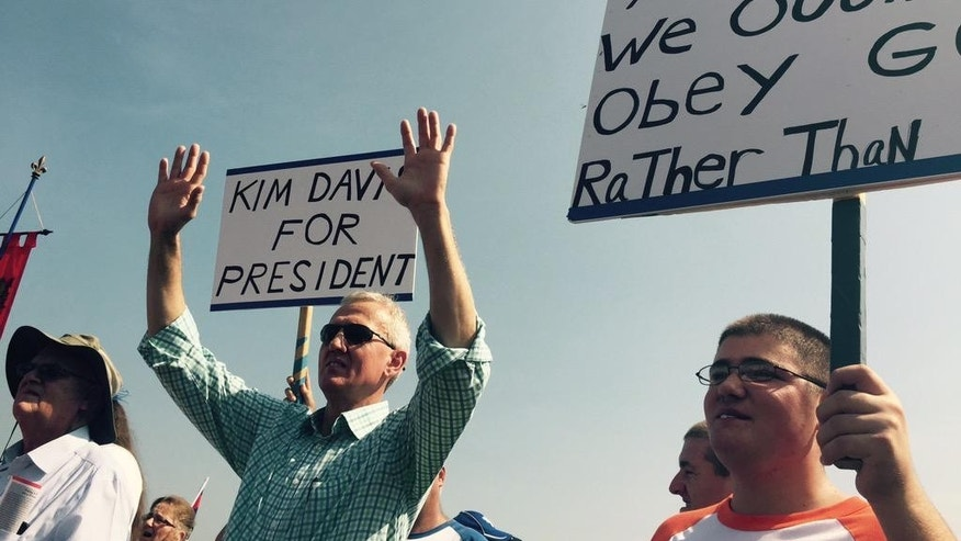 Supporters of Rowan County Clerk Kim Davis hold up signs in support of her, outside the Carter County Detention Center, Saturday, Sept. 5, 2015, in Grayson, Ky. Since the U.S. Supreme Court legalized gay marriage in June, the vast majority of officials have abided by that ruling. However, Davis stopped issuing marriage licenses to any couple, gay or straight, in defiance of a federal court order, and was sent to jail on Thursday. (Joe Gerth/The Courier-Journal via AP)
