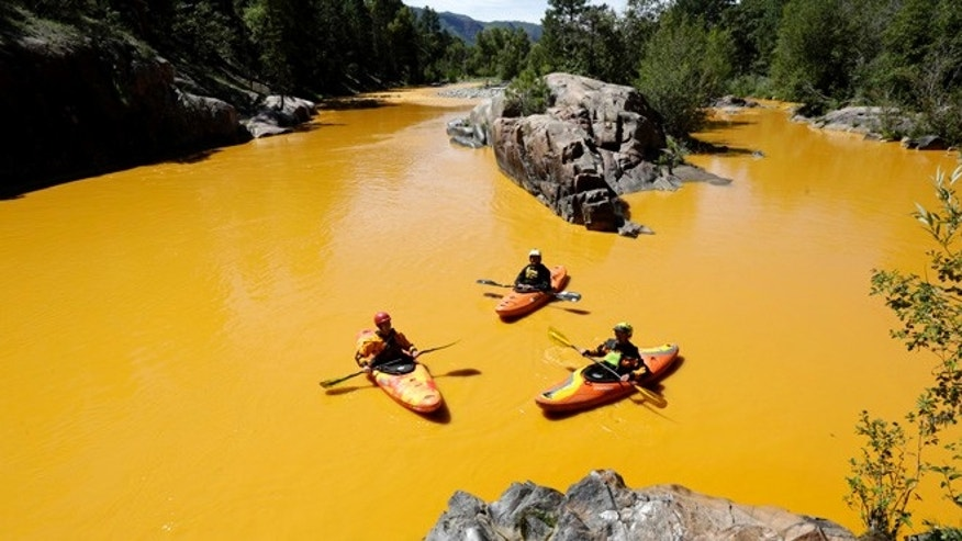 FILE: Aug. 6, 2015: Kayakers in the Animas River near Durango, Colo., in water colored yellow from mine waste spill. (AP)