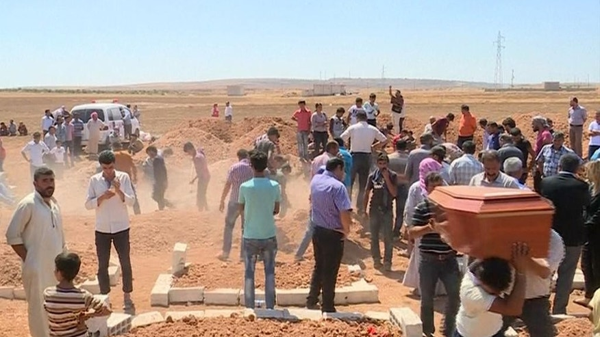 In this image made from video, mourners carry a coffin during the burial of Rehan Kurdi and her sons Aylan, 3, and Galib, 5, after they drowned during a desperate voyage from Turkey to Greece, in their hometown of Kobani, the Syrian Kurdish region they fled, on Friday, Sept. 4, 2015. The haunting image of 3-year-old Aylan Kurdi, washed up on Turkish beach focused the world's attention on the wave of migration fueled by war and deprivation. Their boat capsized while trying to reach the island of Kos. (AP Photo via AP video)