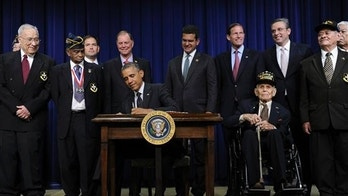 President Barack Obama signs H.R. 1726 to award a Congressional Gold Medal to the 65th Infantry Regiment, know as the Borinqueneers, Tuesday, June 10, 2014, in the South Court Auditorium in the Eisenhower Executive Office Building on the White House complex in Washington.  (AP Photo/Susan Walsh)