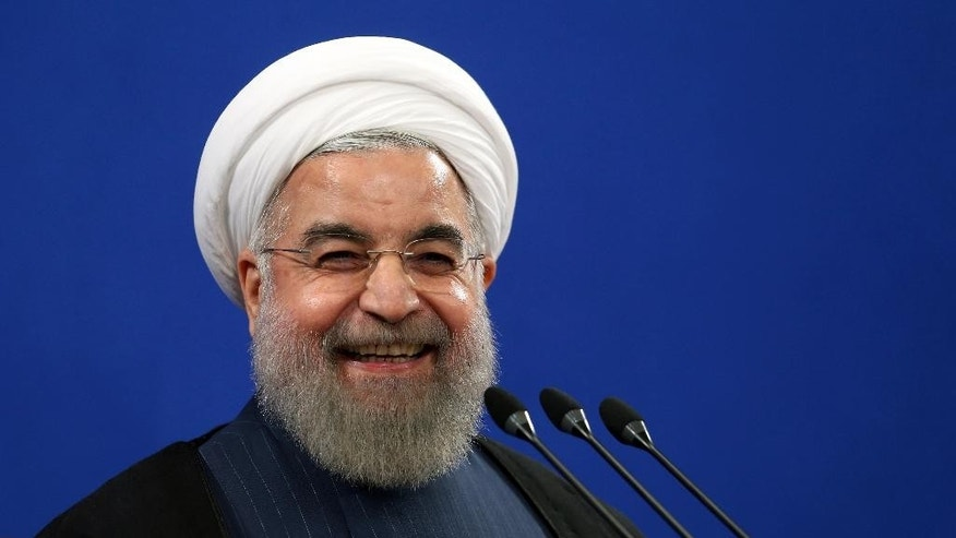 FILE - In this Aug. 29, 2015 file photo, Iran's President Hassan Rouhani smiles during his press conference in Tehran, Iran. Rouhani said Tuesday, Sept. 8, 2015 that his country is ready to hold talks with the United States and Saudi Arabia on ways to resolve the Syrian civil war, providing such negotiations can secure peace and democracy in conflict-torn Syria. Rouhani's remarks came during a press conference on Tuesday with visiting Austrian counterpart Heinz Fischer. (AP Photo/Ebrahim Noroozi, File)