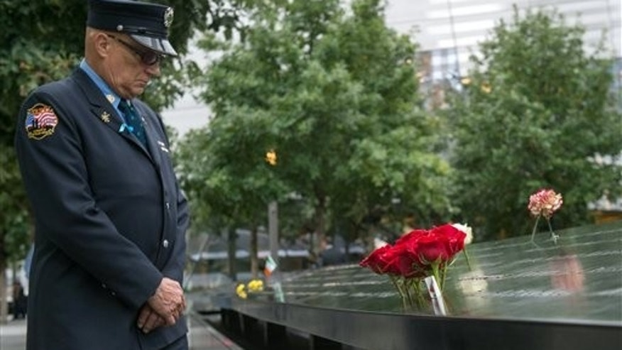 Retired New York City firefighter Joseph McCormick visits the South Pool prior to a ceremony at the World Trade Center site in New York on Friday, Sept. 11, 2015.  (AP Photo/Bryan R. Smith)