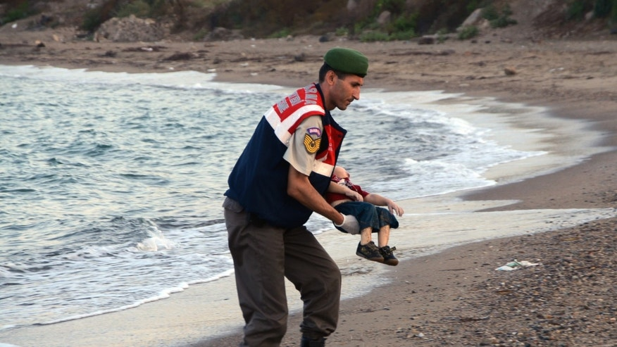 A police officer carries the lifeless body of Aylan Kurdi, 3, in Turkey early Wednesday, Sept. 2, 2015.
