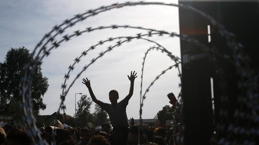 "People protest at the ""Horgos 2"" border crossing into Hungary, near Horgos, Serbia, Wednesday, Sept. 16, 2015. Small groups of migrants continued to sneak into Hungary on Wednesday, a day after the country sealed its border with Serbia and began arresting people trying to breach the razor-wire barrier, while a first group arrived in Croatia seeking another way into the European Union. (AP Photo/Darko Vojinovic)"