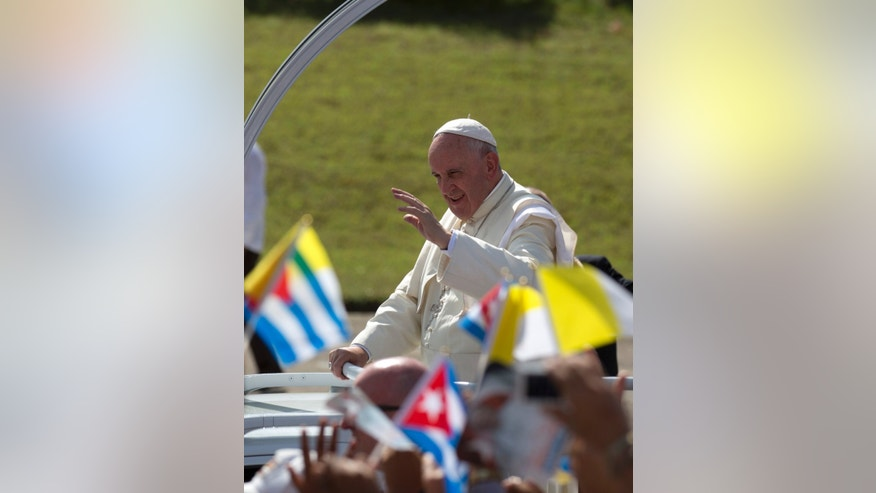 Pope Francis waves from his popemobile as he arrives for Mass at the Plaza of the Revolution in Holguin, Cuba, Monday, Sept. 21, 2015. Holguin's plaza was packed with thousands of people waving flags as Francis traveled in his popemobile through the crowd. Francis is the first pope to visit Holguin, Cuba's third-largest city. (AP Photo/Eduardo Verdugo)