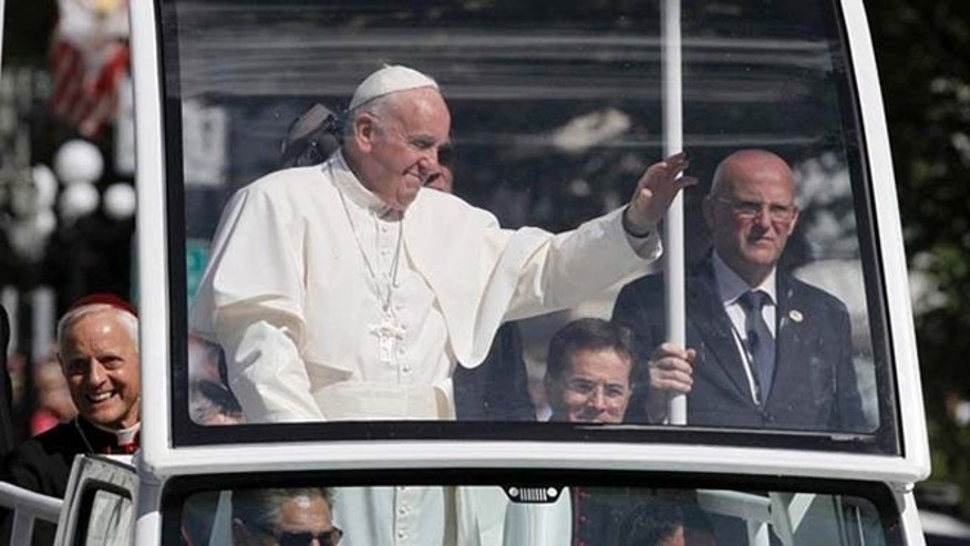 Pope Francis waves from the popemobile during a parade in Washington. (AP)