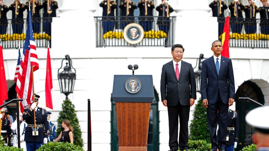 President Barack Obama and Chinese President Xi Jinping stand at attention for the playing of each counties national anthem during an official state arrival ceremony for the Chinese president, Friday, Sept. 25, 2015, on the South Lawn of the White House in Washington.  (AP Photo/Evan Vucci)