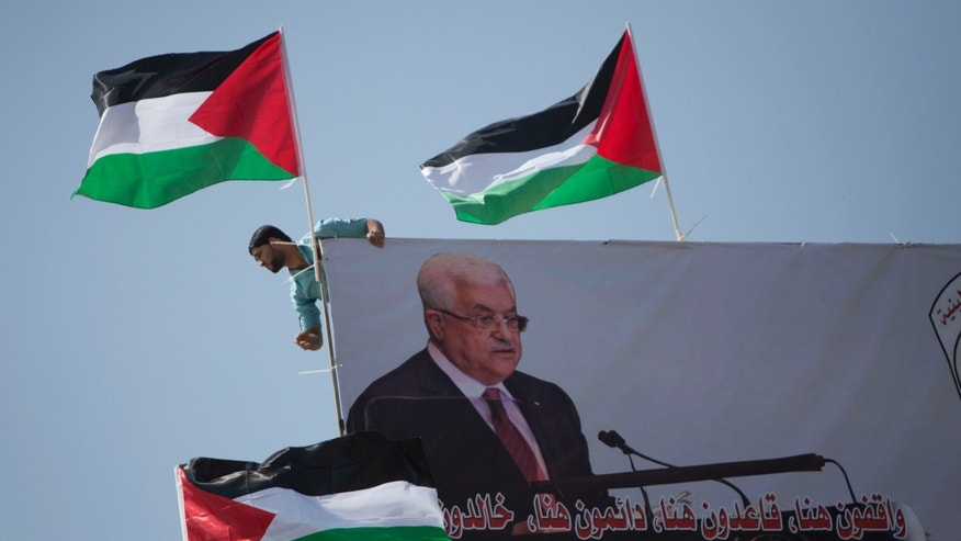 Sept. 30, 2015: A Palestinian installs national flags above the poster of Palestinian President Mahmoud Abbas in the West Bank city of Nablus. A Palestinian installs national flags above the poster of Palestinian President Mahmoud Abbas in the West Bank city of Nablus. Wednesday, Sept. 30, 2015. (AP Photo/Majdi Mohammed)