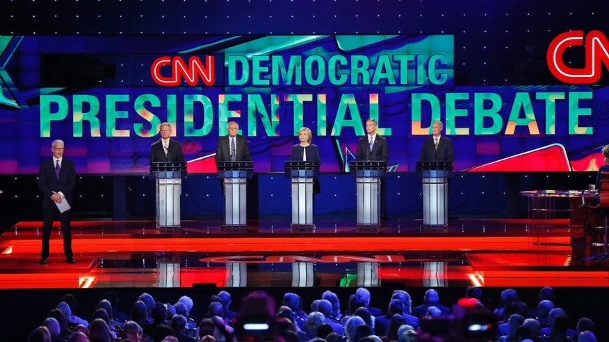 Democratic presidential candidates from left, former Virginia Sen. Jim Webb, Sen. Bernie Sanders, of Vermont, Hillary Rodham Clinton, former Maryland Gov. Martin O'Malley, and former Rhode Island Gov. Lincoln Chafee take the stage before the CNN Democratic presidential debate Tuesday, Oct. 13, 2015, in Las Vegas. On the far left is moderator Anderson Cooper.  (AP Photo/John Locher)
