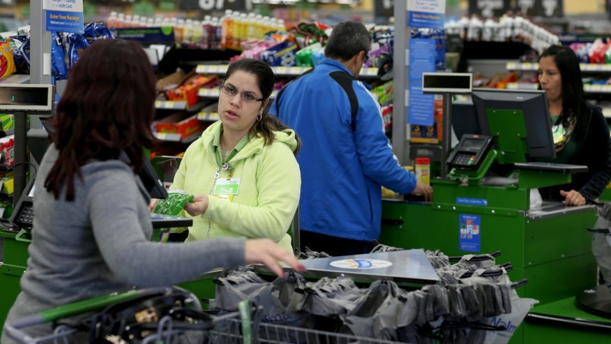 MIAMI, FL - FEBRUARY 19:  Walmart employee Adriana Cajuso (2L) rings up the purchases of customer Yoalmi Matias as she checks-out at a Walmart store on February 19, 2015 in Miami, Florida.  The Walmart company announced Thursday that it will raise the wages of its store employees to $10 per hour by next February, bringing pay hikes to an estimated 500,000 workers.  (Photo by Joe Raedle/Getty Images)