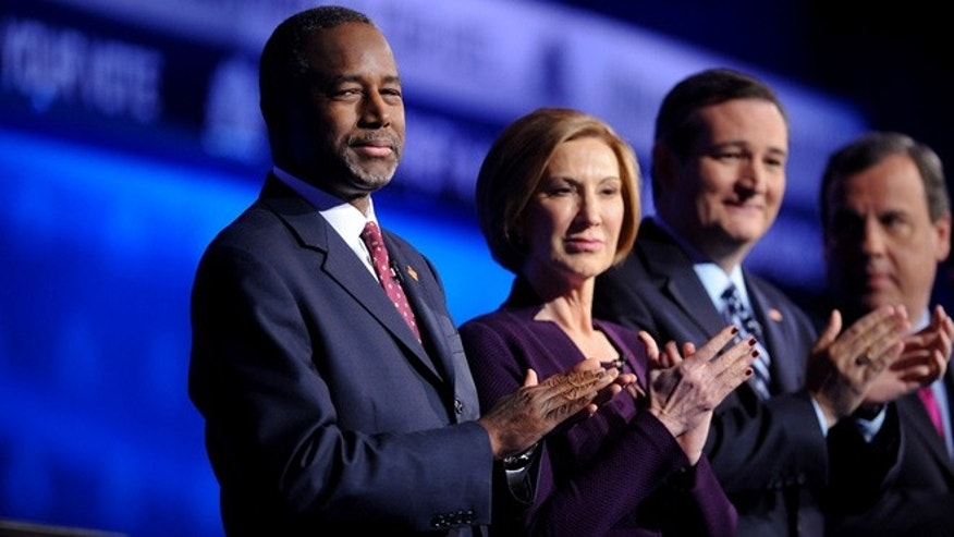 Republican U.S. presidential candidate Dr. Ben Carson (L) looks back as he stands with former HP CEO Carly Fiorina, U.S. Senator Ted Cruz and Governor Chris Christie (R) before the start of the 2016 U.S. Republican presidential candidates debate.