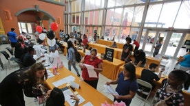 In this Tuesday, Oct. 6, 2015 photo, job applicants fill out and turn in forms during a job fair at Dolphin Mall in Miami. The U.S. Labor Department reports on the number of people who applied for unemployment benefits during the week ending Oct. 17 on Thursday, Oct. 22, 2015. (AP Photo/Wilfredo Lee)