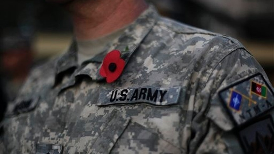 FILE -- An American soldier wears a poppy emblem stuck to his uniform during a ceremony marking Veterans Day at the U.S. Camp Eggers in Kabul, Afghanistan. (AP Photo/Anja Niedringhaus)