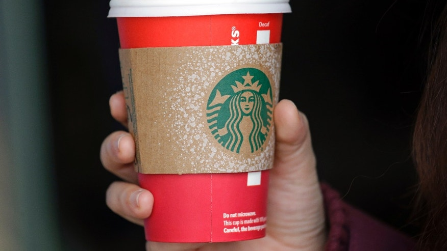 Nov. 10, 2015 - Customer carries coffee in a red cup outside Starbucks coffee shop at Pike Place Market in Seattle. (AP)