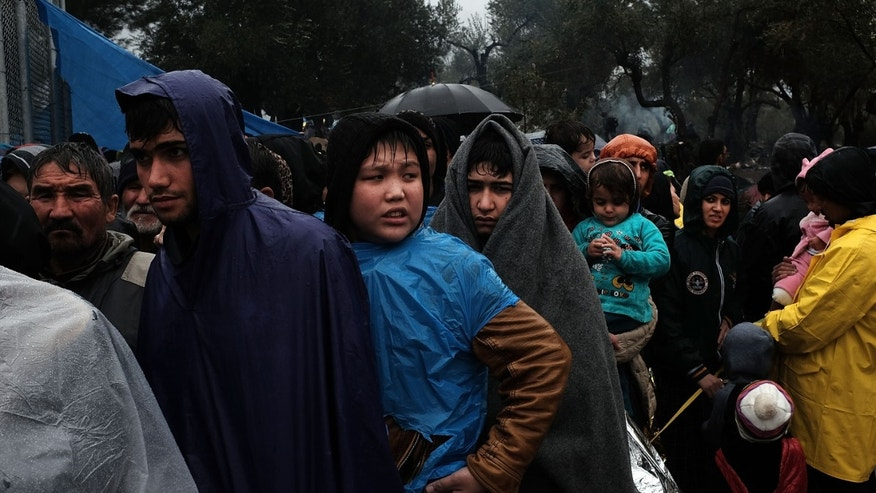 Migrants try to stay dry and warm at the Moria camp on the island of Lesbos on October 23, 2015 in Mitilini, Greece.