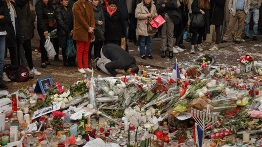 Nov. 20, 2015 - People commemorate the victims of extremists attacks outside the Carillon Hotel in Paris. French Pres Francois Hollande will preside over a ceremony Nov. 27 honoring the 130 victims of the deadliest attacks on France in decades. (AP)