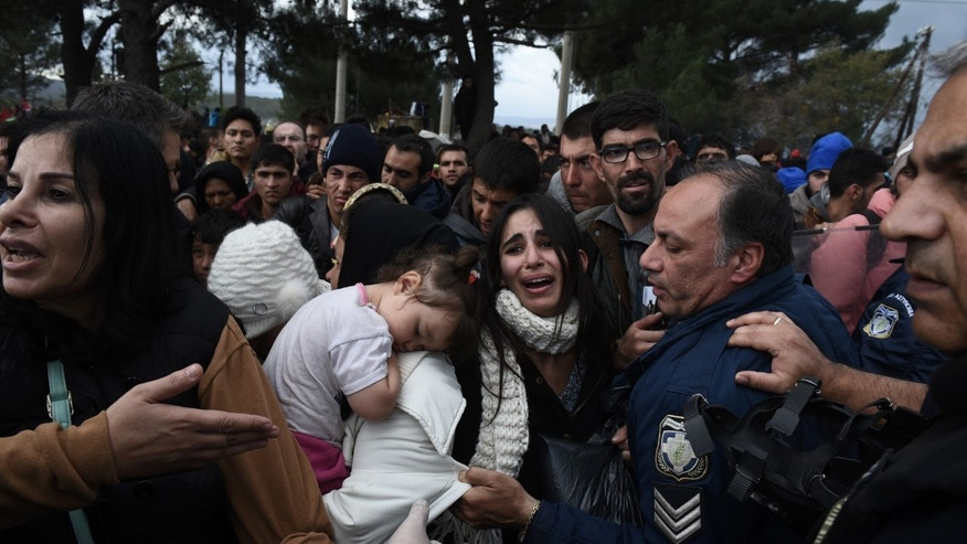 A woman cries as refugees scuffle with the Greek police in their effort to reach the borderline with Macedonia, near the Greek village of Idomeni, Sunday, Nov. 22, 2015. About 1,300 migrants gathered in the Greek town Idomeni protested Saturday against the decision by Macedonian authorities across the border to turn away migrants who are not from war zones such as Syria, Afghanistan and Iraq. (AP Photo/Giannis Papanikos)