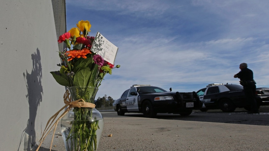 Flowers are left by the side of the road as a San Bernardino police officer blocks the road leading to the site of yesterday's mass shooting on Thursday, Dec. 3, 2015 in San Bernardino, Calif.  A heavily armed man and woman dressed for battle opened fire on a holiday banquet for his co-workers Wednesday, killing multiple people and seriously wounding others in a precision assault, authorities said. Hours later, they died in a shootout with police. (AP Photo/Chris Carlson)