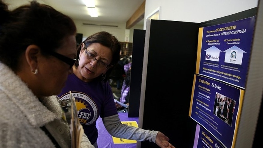 RICHMOND, CA - MARCH 31:  A worker explains the process for registering during a healthcare enrollment fair at the Bay Area Rescue Mission on March 31, 2014 in Richmond, California. SEIU-United Healthcare Workers West (SEIU-UHW) held the fair to help people sign up for free and low-cost health coverage through Medi-Cal or Covered California on the final day before the sign-up deadline.  (Photo by Justin Sullivan/Getty Images)