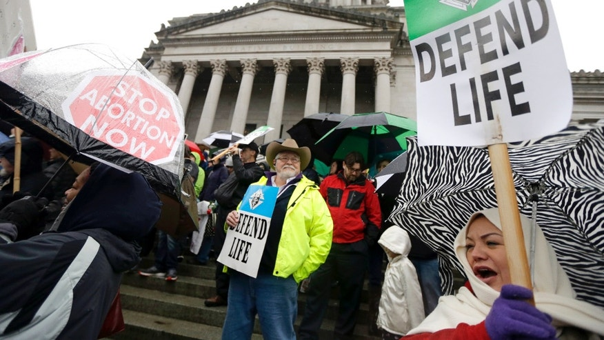 Anti-abortion demonstrators take part in a rally, Tuesday, Jan. 19, 2016, at the Capitol in Olympia, Wash. (AP Photo/Ted S. Warren)