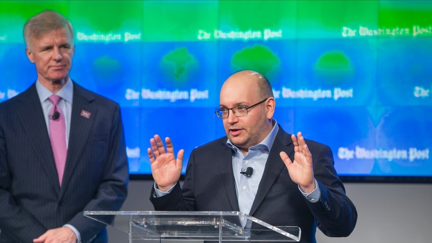 Freed Washington Post reporter Jason Rezaian, center, joined by Post Publisher Frederick Ryan speaks about his release from a Tehran jail in a prisoner swap this month, as he returns to his newspaper for the opening ceremony of the new headquarters of The Washington Post, Thursday, Jan. 28, 2016, in Washington.  (AP Photo/J. Scott Applewhite)
