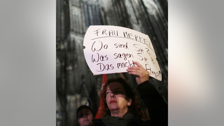 "A woman protests  against sexism outside the cathedral in Cologne, Germany,  Tuesday Jan. 5, 2016.  Poster reads "" Mrs. Merkel. Where are you? What do you say? It's scary"".  German Chancellor Angela Merkel voiced outrage Tuesday at a series of sexual assaults in the western city of Cologne on New Year's Eve, saying the perpetrators need to be found as soon as possible. Merkel called Cologne's mayor Henriette Reker to express her concern about the assaults, which took place around Cologne's main train station, next to the city's famous cathedral.   (Oliver Berg/dpa via AP)"