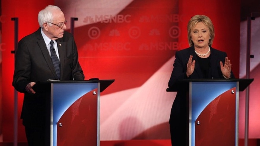 Democratic U.S. presidential candidate Senator Bernie Sanders (L) listens to former Secretary of State Hillary Clinton speak during the Democratic presidential candidates debate sponsored by MSNBC at the University of New Hampshire in Durham, New Hampshire, February 4, 2016. REUTERS/Mike Segar - RTX25IQ6