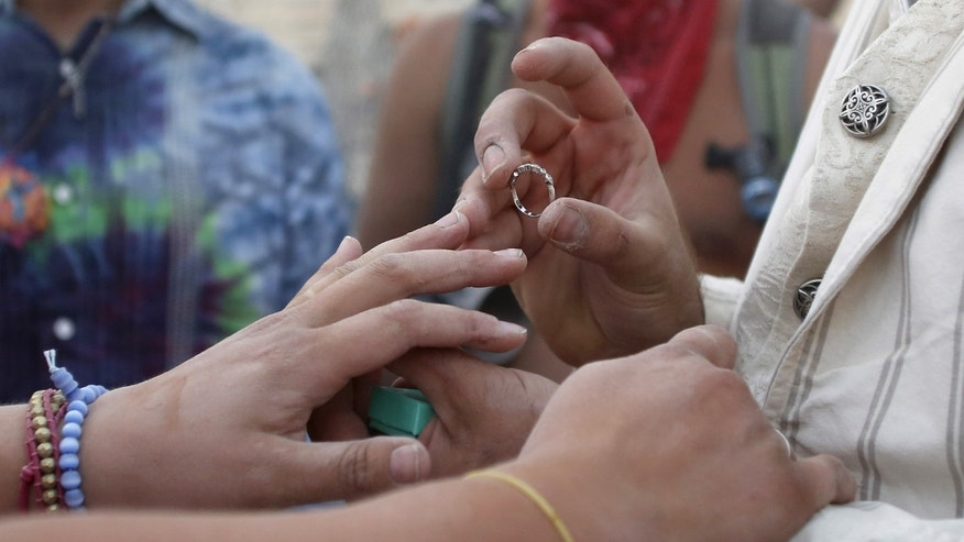 September 2, 2015– Groom places a ring on bride's finger at a wedding ceremony in Nevada. (REUTERS)