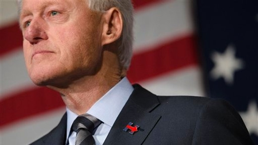 Former President Bill Clinton wears a campaign pin for his wife, Democratic presidential candidate Hillary Clinton, as he campaigns for her on Feb. 12, 2016, at the Clifton Cultural Arts Center in Cincinnati. (AP Photo/John Minchillo)