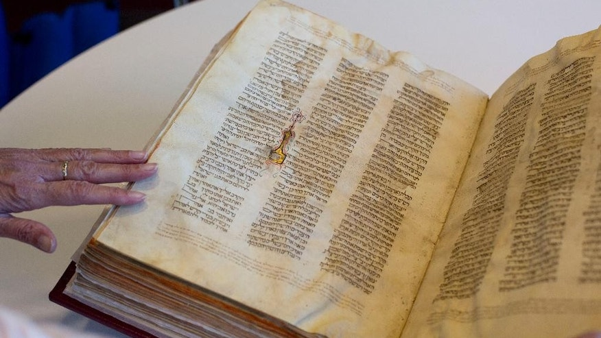 FILE - In this  Oct. 5, 2014 file photo, a library official shows a Jewish manuscript smuggled into Israel from Damascus in a Mossad spy operation in the early 1990s, in Jerusalem. The manuscript is one of the earliest existing complete manuscripts of the Hebrew bible. Two decades after Israeli spies helped whisk eight ancient Hebrew bibles from Damascus to Jerusalem, Israel's national library asked an Israeli court Monday, Dec. 8, 2014 to grant it official custodianship over the manuscripts, a move that is liable to spark a bitter ownership battle over the some of the Syrian Jewish community's most important treasures. (AP Photo/Sebastian Scheiner, File)