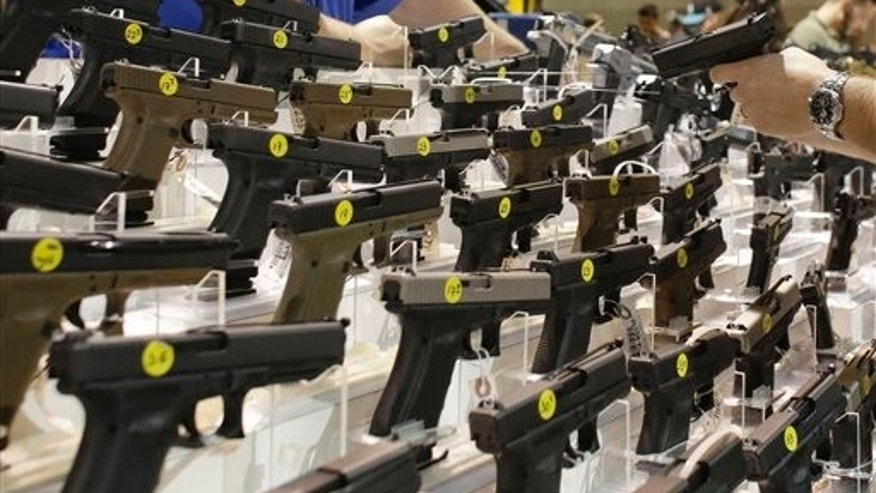 FILE - A customer looks at a pistol at a vendor's display at a gun show held by Florida Gun Shows in Miami on Saturday, Jan. 9, 2016. States enter data into the national background check system about people who are convicted of crimes that disqualify them from buying guns. That information turns up when licensed dealers conduct background checks and has resulted in more than 120,000 applicants being denied since 1998 for having misdemeanor domestic violence convictions. (AP Photo/Lynne Sladky)