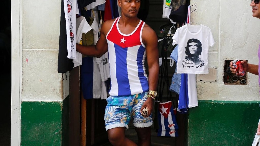 FILE -- June 1, 2015: A vendor wearing a shirt with a Cuban national flag motif, stands next to a souvenir T-shirt featuring Che Guevara, in the shop's doorway, in Old Havana, Cuba.