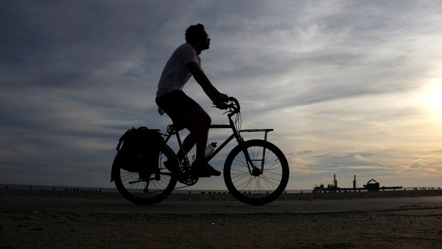 FILE -- Sept. 24, 2015: A commuter cruises on his bike on a trail along Lake Michigan, in Chicago.  (AP)