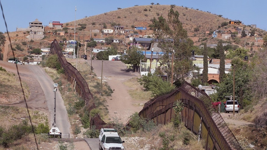 NOGALES, AZ - JUNE 02:  A U.S. U.S. Customs and Border Protection agent drives along a fence which separates the cities of Nogales, Arizona and Nogales, Sonora Mexico, a frequent crossing point for people entering the United States illegally, June 2, 2010 in Nogales, Arizona.  During the 2009 fiscal year 540,865 undocumented immigrants were apprehended entering the United States illegally along the Mexican border, 241,000 of those were captured in the 262 mile stretch of the border known as the Tucson Sector.  (Photo by Scott Olson/Getty Images)