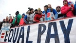 Fans stand behind a large sign for equal pay for the women's soccer team during an international friendly soccer match between the United States and Colombia at Pratt & Whitney Stadium at Rentschler Field, Wednesday, April 6, 2016, in East Hartford, Conn. (AP Photo/Jessica Hill)
