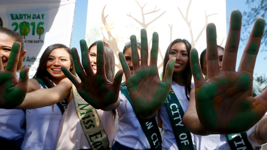 "Friday, April 22, 2016: Miss Earth beauty contestants show their painted hands prior to joining coastal clean up to mark World Earth Day at a bird sanctuary known as ""Freedom Island"" in suburban Las Pians city, south of Manila, Philippines. (AP Photo/Bullit Marquez)"