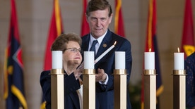 Holocaust survivor Rose Reichbach, left, is assisted by Rep. Don Beyer D-Va. in lighting a candle as the U.S. Holocaust Memorial Museum holds its annual Days of Remembrance Ceremony, on Capitol Hill in Washington, Thursday, May 5, 2016, to honor the victims of the Holocaust and Nazi persecution. Rose Reichbach and her family fled from their native Poland to Belarus during the Nazi invasion. She and her parents were sent to gulags in Siberia and later to Kyrgyzstan. After the war, she immigrated to Israel and later settled in Washington, DC. (AP Photo/J. Scott Applewhite)