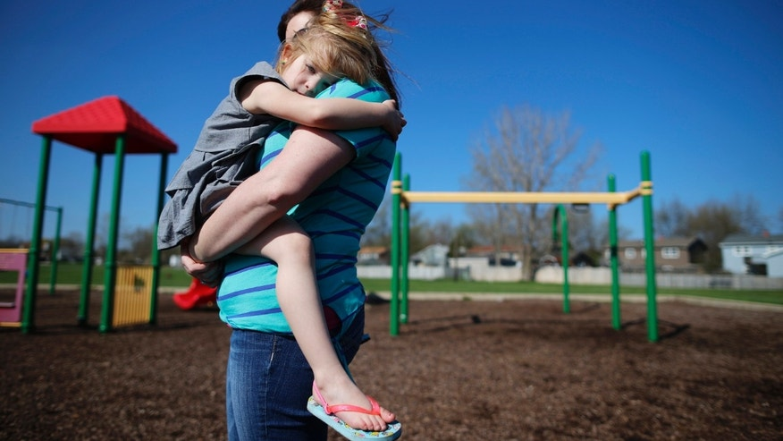 ILE -- May 9, 2014: Andrea Smith holds her daughter Norah at a playground in Winthrop Harbor, Illinois. (Reuters)